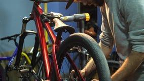 Νέος ένας mahanic καθορίζοντας μια ρόδα ποδηλάτων στο εργαστήριο επισκευής της φιλμ μικρού μήκους