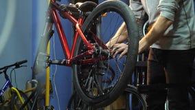 Νέος ένας mahanic καθορίζοντας μια ρόδα ποδηλάτων στο εργαστήριο επισκευής της απόθεμα βίντεο