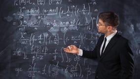 Νέος έξυπνος αρσενικός δάσκαλος ή σπουδαστής που εξηγεί την απόφαση της σκληρής εξίσωσης math φιλμ μικρού μήκους