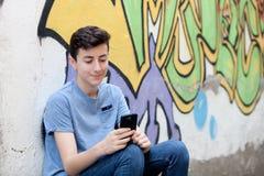 Νέος έφηβος με το τηλέφωνο κυττάρων της Στοκ φωτογραφία με δικαίωμα ελεύθερης χρήσης