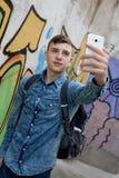 Νέος έφηβος με το τηλέφωνο κυττάρων της Στοκ Φωτογραφίες