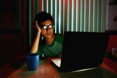 Νέος έφηβος με eyeglasses και τρυπημένος μπροστά από έναν φορητό προσωπικό υπολογιστή Στοκ Εικόνα