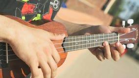 Νέος έφηβος που παίζει μια ακουστική κιθάρα υπαίθρια απόθεμα βίντεο