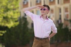 Νέος έφηβος που χαμογελά με το χέρι του στο μάτι Στοκ Εικόνες