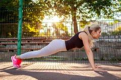 Νέος αθλητής γυναικών που κάνει το ώθηση-UPS στο sportsground το καλοκαίρι σανίδα Υγιής τρόπος ζωής Ασκήσεις πρωινού στοκ φωτογραφία με δικαίωμα ελεύθερης χρήσης