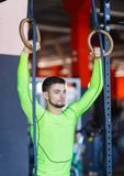 Νέος αθλητής με τα γυμναστικά δαχτυλίδια στη γυμναστική στοκ φωτογραφία με δικαίωμα ελεύθερης χρήσης