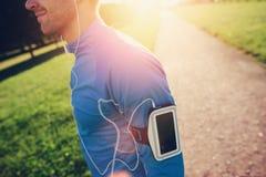 Νέος αθλητής με armband που κοιτάζει προς τα εμπρός στο πάρκο Στοκ Εικόνες