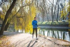 Νέος αθλητής που τρέχει στο πάρκο το κρύο ηλιόλουστο πρωί φθινοπώρου Υγιής έννοια τρόπου ζωής και αθλητισμού Στοκ εικόνα με δικαίωμα ελεύθερης χρήσης