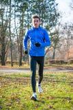 Νέος αθλητής που τρέχει στο πάρκο το κρύο ηλιόλουστο πρωί φθινοπώρου Υγιής έννοια τρόπου ζωής και αθλητισμού Στοκ φωτογραφίες με δικαίωμα ελεύθερης χρήσης
