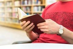 Νέος αθλητικός άτομο ή σπουδαστής που διαβάζει ένα βιβλίο δημόσια ή το σχολείο στοκ φωτογραφία