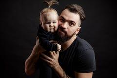 Νέος αθλητικός πατέρας με το λατρευτό μωρό στο μαύρο υπόβαθρο στοκ εικόνα με δικαίωμα ελεύθερης χρήσης
