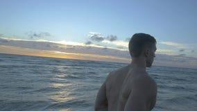 Νέος αθλητικός τύπος που τρέχει στην παραλία θάλασσας στο ηλιοβασίλεμα σε αργή κίνηση πίσω άποψη απόθεμα βίντεο