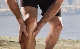 Νέος αθλητής με τα αθλητικά πόδια που κρατά το γόνατο στον πόνο που υφίσταται το τρέξιμο τραυματισμών μυών