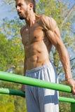 Νέος αθλητής που επιλύει σε μια υπαίθρια γυμναστική Ασκήσεις Workout οδών Ανήσυχοι μυ'ες Στοκ εικόνες με δικαίωμα ελεύθερης χρήσης