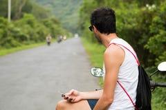 Νέος αναβάτης τουριστών με τα γυαλιά ηλίου που περιμένουν στη μοτοσικλέτα του και που ελέγχουν ένα smartphone στοκ φωτογραφίες