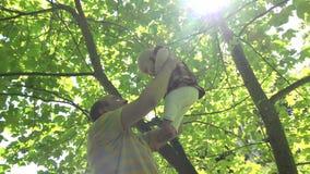Νέος ανελκυστήρας πατέρων και ευτυχές κορίτσι κορών μωρών φιλιών κάτω από το δέντρο τουλιπών 4K απόθεμα βίντεο