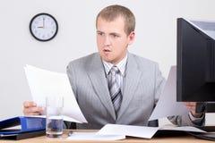Νέος ανησυχημένος λογιστής που κάνει τη γραφική εργασία στην αρχή Στοκ φωτογραφίες με δικαίωμα ελεύθερης χρήσης