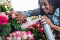 Νέος ανθοκόμος αφροαμερικάνων που ψεκάζει τα όμορφα λουλούδια Στοκ Φωτογραφία