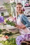 Νέος ανθοκόμος που κρατά τα όμορφα λουλούδια και που κοιτάζει μακριά στο ανθοπωλείο Στοκ φωτογραφία με δικαίωμα ελεύθερης χρήσης