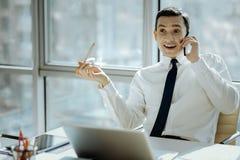 Νέος ανώτερος υπάλληλος που αντιδρά ευτυχώς στις καλές ειδήσεις στο τηλέφωνο Στοκ Εικόνα