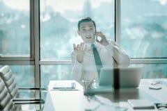 Νέος ανώτερος υπάλληλος που διαπραγματεύεται συναισθηματικά στο τηλέφωνο Στοκ Εικόνες