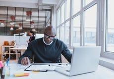 Νέος ανώτερος υπάλληλος στο γραφείο του που διαβάζει ένα έγγραφο στοκ εικόνες