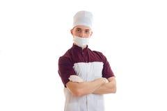 Νέος απόφοιτος φοιτητής γιατρών με το καπέλο στο κεφάλι του και μια μάσκα στο πρόσωπο Στοκ εικόνα με δικαίωμα ελεύθερης χρήσης