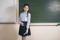 Νέος αρκετά θηλυκός δάσκαλος χρησιμοποιώντας την κατηγορία μελέτης διδασκαλίας ραβδιών και στεμένος στο υπόβαθρο πινάκων κιμωλίας Στοκ φωτογραφία με δικαίωμα ελεύθερης χρήσης