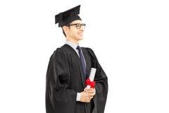 Νέος αρσενικός απόφοιτος φοιτητής που κρατά ένα δίπλωμα Στοκ φωτογραφία με δικαίωμα ελεύθερης χρήσης