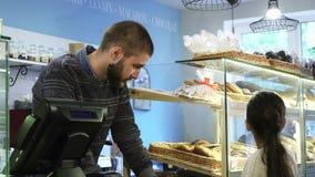 Νέος αρσενικός αρτοποιός που εργάζεται στο κατάστημά του που βοηθά το μικρό κορίτσι που επιλέγει τα επιδόρπια απόθεμα βίντεο