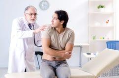 Νέος αρσενικός ασθενής που επισκέπτεται τον παλαιό γιατρό στοκ φωτογραφίες με δικαίωμα ελεύθερης χρήσης