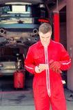 Νέος αρσενικός αυτόματος μηχανικός που στέκεται κάνοντας τις σημειώσεις Στοκ φωτογραφίες με δικαίωμα ελεύθερης χρήσης