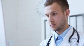 Νέος αρσενικός γιατρός που εξετάζει τη οθόνη υπολογιστή στο γραφείο στην κλινική στοκ φωτογραφία με δικαίωμα ελεύθερης χρήσης