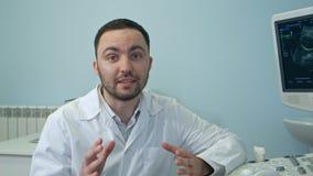 Νέος αρσενικός γιατρός που μιλά στη συνεδρίαση καμερών δίπλα στη μηχανή ανίχνευσης υπερήχου Στοκ Εικόνα