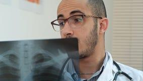 Νέος αρσενικός γιατρός στα γυαλιά που αναλύουν προσεκτικά την των ακτίνων X εικόνα Στοκ Φωτογραφία