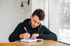 Νέος αρσενικός επιχειρηματίας που γράφει σε ένα σημειωματάριο στο ξύλινο γραφείο στο κατάστημα καφέδων καφέ Στοκ Εικόνα
