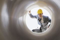 Νέος αρσενικός επόπτης που εξετάζει το μεγάλο σωλήνα στο εργοτάξιο οικοδομής Στοκ εικόνες με δικαίωμα ελεύθερης χρήσης