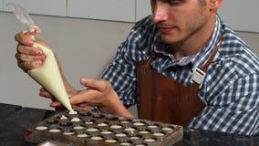 Νέος αρσενικός ζαχαροπλάστης που προσθέτει την πλήρωση βανίλιας στις φόρμες καραμελών σοκολάτας απόθεμα βίντεο
