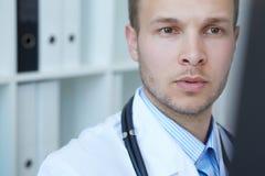 Νέος αρσενικός ιατρός που εξετάζει την των ακτίνων X εικόνα στην κλινική στοκ εικόνες