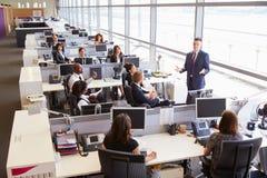 Νέος αρσενικός διευθυντής που απευθύνεται στους εργαζομένους στο ανοικτό γραφείο σχεδίων Στοκ Εικόνα