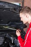 Νέος αρσενικός μηχανικός μηχανών που ελέγχει το επίπεδο πετρελαίου σε ένα αυτοκίνητο Στοκ φωτογραφία με δικαίωμα ελεύθερης χρήσης