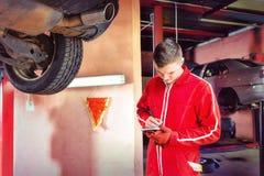 Νέος αρσενικός μηχανικός μηχανών που στέκεται κάνοντας τις σημειώσεις κάτω από ένα lif Στοκ εικόνα με δικαίωμα ελεύθερης χρήσης