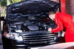 Νέος αρσενικός μηχανικός μηχανών στο ομοιόμορφο αυτοκίνητο ελέγχου και καθορισμού eng Στοκ εικόνα με δικαίωμα ελεύθερης χρήσης