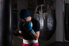 Νέος αρσενικός μπόξερ σε ένα καπέλο και εγκιβωτίζοντας γάντια που εκπαιδεύουν με τον εγκιβωτισμό Στοκ Φωτογραφία