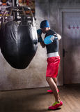 Νέος αρσενικός μπόξερ στα εγκιβωτίζοντας γάντια που εκπαιδεύει με τον εγκιβωτισμό punching Στοκ φωτογραφίες με δικαίωμα ελεύθερης χρήσης