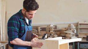Νέος αρσενικός ξυλουργός που εργάζεται στο ξύλινο εργαστήριο απόθεμα βίντεο