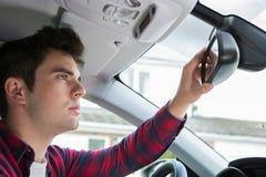 Νέος αρσενικός οδηγός στο αυτοκίνητο που ελέγχει τον οπισθοσκόπο καθρέφτη Στοκ Εικόνα