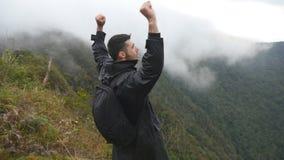 Νέος αρσενικός οδοιπόρος με το σακίδιο πλάτης που φθάνει επάνω στην κορυφή του βουνού και των αυξημένων χεριών Τουρίστας ατόμων π φιλμ μικρού μήκους