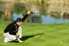 Νέος αρσενικός παίκτης γκολφ που παρατάσσει Putt στοκ φωτογραφίες