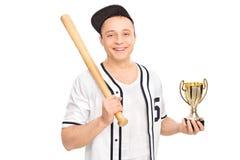 Νέος αρσενικός παίχτης του μπέιζμπολ που κρατά ένα τρόπαιο Στοκ Εικόνες